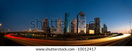 Houston skyline against blue sky after sunset surrounded by lights of highway traffic