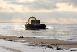 Hovercraft flying above water. Air cushion sailing near beach. Yellow hover craft under way.