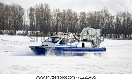 Hovercraft rides on the frozen river, picking up snow dust. Winter