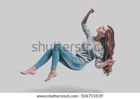 Hovering beauty. Full length studio shot of attractive young woman hovering in air and keeping eyes closed