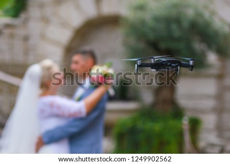 Hovering drone taking pictures of wedding couple in nature