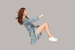 Hovering in air. Amazed girl levitating in driving seat position, holding invisible steering wheel, looking shocked, open mouth surprised by high speed, watching unbelievable. studio shot isolated
