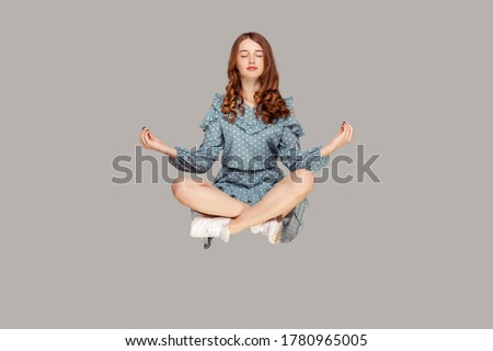 Hovering in air. Calm peaceful relaxed girl ruffle dress levitating with mudra gesture hands up, closed eyes, meditating sitting in yoga position. indoor studio shot isolated on gray background
