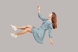 Hovering in air. Cheerful smiling pretty girl in vintage ruffle dress levitating flying in mid-air, looking up happy dreamy and raising hand to catch. indoor studio shot isolated on gray background