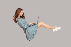 Hovering in air. Pretty girl ruffle dress levitating, typing keyboard using laptop for work online, surfing web social networks while flying in mid-air. indoor studio shot isolated on gray background