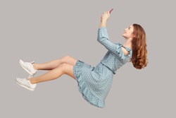 Hovering in air. Smiling girl ruffle dress levitating with mobile phone, reading message chatting happy joyful in social network online, surfing web while flying. indoor studio shot isolated on gray