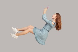 Hovering in air. Surprised shocked girl ruffle dress levitating with mobile phone, chatting online in social network amazed by unbelievable news message, surfing web while flying. studio shot isolated