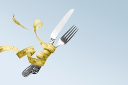 Hovering in the air fork and knife wrapped in a centimeter tape. The concept of proper, balanced nutrition, diet. To lose weight.