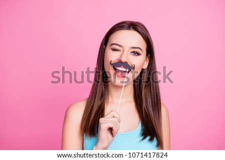How are you doing? Portrait of charming joyful tender cheerful childish cute lovely cool woman with brown hairdress holding fake mustache on stick over mouth and winking, isolated on pink background
