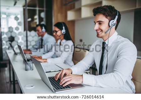 How can I help you? Beautiful call center workers in headphones are working at modern office. #726014614