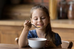 How tasty. Cute little girl enjoy eating cereal for morning breakfast with appetite. Hungry child holding full table spoon of sweet delicious corn oat flakes with milk honey feeling pleasure delight
