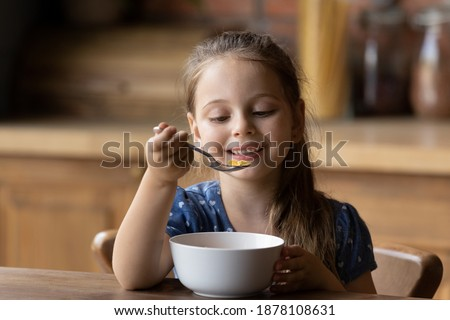 How tasty. Cute little girl enjoy eating cereal for morning breakfast with appetite. Hungry child holding full table spoon of sweet delicious corn oat flakes with milk honey feeling pleasure delight Stock photo ©