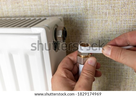 How to connect a faucet to a heating radiator. Step by step instructions. Step 5. Selective focus. Photo stock ©