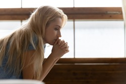 How to deal with it? Side shot of thoughtful pensive sad young female sitting indoors leaning forward propping chin on clasped hands feeling desperate, unhappy, tired, lost, disappointed. Copy space