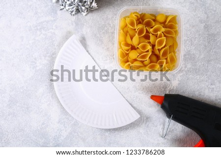 How to make a Christmas tree from raw pasta conchiglie. The process of making Christmas trees from pasta, cardboard plates, hot glue and paint or spray. Guide, step by step on the photo.Handmade, DIY. #1233786208