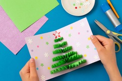 How to make Christmas card with volumetric tree. Original project for children. DIY concept. Step-by-step photo instructions. Step 9. Decorate card with confetti and snowflakes