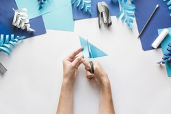 How to make paper beautiful Christmas toy snowflake to decorate room with children at home. Step by step instructions. Hands making DIY winter craft project. Step 5. Cut the sheet from mark to line