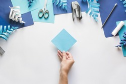 How to make paper beautiful Christmas toy snowflake to decorate room with children at home. Step by step instructions. Hands making DIY winter craft project. Step 1. Take square sheet of colored paper