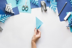 How to make paper beautiful Christmas toy snowflake to decorate room with children at home. Step by step instructions. Hands making DIY winter craft project. Top view. Step 2. Fold sheet diagonally