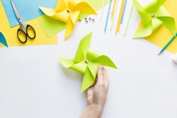 How to make paper green windmill toy with children at home. Step by step instructions. Hands making DIY summer project. Top view. Step 10. Attach push pin to mark center of pinwheel