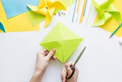 How to make paper green windmill toy with children at home. Step by step instructions. Hands making DIY summer project. Step 5. Cut sheet in lines to circle in center, getting half-cut triangles