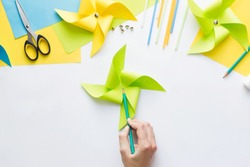How to make paper green windmill toy with children at home. Step by step instructions. Hands making DIY summer project. Step 9. Mark center of resulting figure, capturing all the edges of triangles