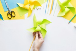 How to make paper green windmill toy with children at home. Step by step instructions. Hands making DIY summer project. Top view. Step 12. Enjoy ready pinwheel toy