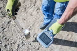 How to trace power cables with the cable Finder. Electric technical worker with power cable fault location carries out a work of tracing the new electric line with a colored spray can.
