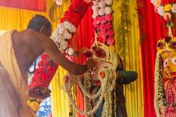 Howrah, West Bengal, India - 29th June 2020 : Hindu priest putting holy ash of yajna on idol of God Balaram as ritual, for worshipping idol of God Jagannath, Balaram and Suvodra inside pandal.