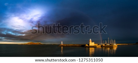Howth Harbour in Dublin panorama under a dramatic stormy cloudy sky and rainbow spreading from the Eye of Ireland across to a lighthouse and moored sailing boats bathed in sunlight. Copy space.