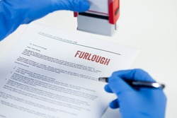 HR hand in blue protective glove stamping FURLOUGH notice letter,temporary unpaid leave,absence of employees due to lack of work in company,UK government measure to help laid off staff during lockdown