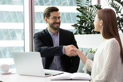 Hr manager headhunter greeting female vacancy candidate applicant people sitting at modern office table shaking hands start job interview. Company client and agent handshaking begin formal meeting