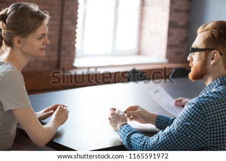 HR manager talking with smiling female job candidate during work interview in office, recruiter considering applicant resume, thinking about her candidature for position. Employment concept