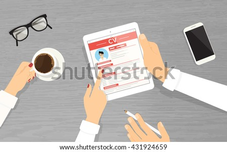 HR managers searching an employee using tablet pc in the office.  Employers are looking at the tablet pc display and reading new employer  cv. Top view with textured table, smartphone and coffee mug