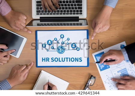 HR SOLUTIONS Business team hands at work with financial reports and a laptop, top view