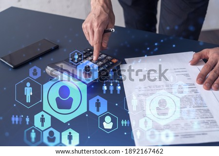 HR specialist researching and analyzing the data of salary on employment market to forecast ongoing expenses of the company using calculator. Hiring new talented officers. Social media hologram icons