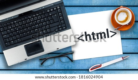HTML Hyper Text Markup Language. Paper width html tag and laptop, glasses and coffee on wooden table  Stock fotó ©
