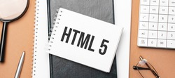 html 5 on notepad and various business papers on brown background. Brown glasses and magnifier with notepad.