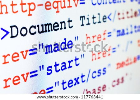 HTML source code of web page with document title, metadata description and links monitor screenshot diagonal view, small depth of sharpness