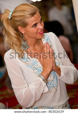 HUA HIN, THAILAND - JUNE 28: Kim Kotter former Miss Netherlands Universe 2002 pays respect to an abbot at Huaymongkol Temple during Miss Netherlands 2011 Boot-camp on June 28 2011 in Hua Hin, Thailand