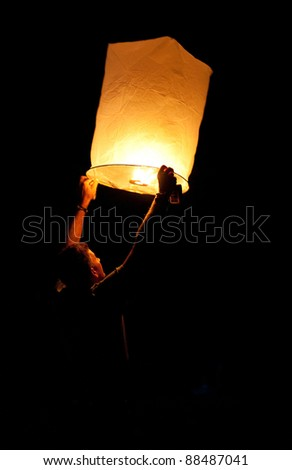 Hua Hin, THAILAND - NOVEMBER 21: People holding a flying fire lantern to celebrate the Loy Krathong festival. November 21, 2010 in Hua Hin, Thailand.