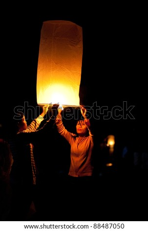 Hua Hin, THAILAND - NOVEMBER 21: Two people holding a flying fire lantern to celebrate the Loy Krathong festival. November 21, 2010 in Hua Hin, Thailand.