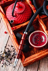 Hubble-bubble.Details of smoking hookah,cast iron red teapot in wooden box