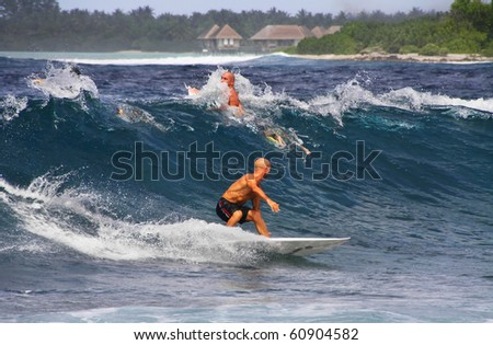 HUDHURANFUSHI ISLAND, MALDIVES - JULY 1: Unidentified men surfing on  waves of Indian Ocean of Maldives on 1 July 2009 Hudhuranfushi island is very popular place for surfers from all over the world.