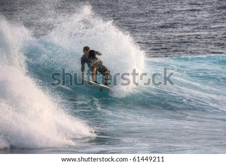 HUDHURANFUSHI ISLAND,MALDIVES-JUNE 29:Unidentified man surfing on huge wave of Indian Ocean of Maldives on June 29, 2009 in Hudhuranfushi. The island is a popular place for surfers from over the world - stock photo