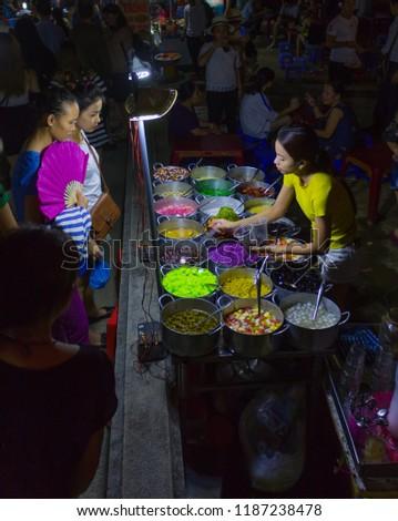 Hue, Vietnam, August 4th 2017.  Bustling night market under a bridge next to the Perfume River in Hue, Vietnam.