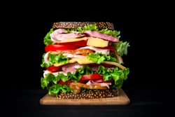 Huge appetizing sandwich on a black background.