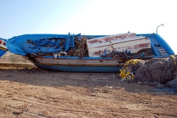 Huge boat broken over the land. Lampedusa, summer 2009.