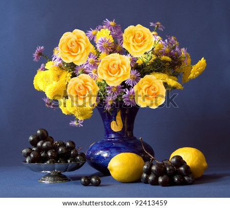 Huge bunch of autumn flowers and yellow roses, lemon and grapes on dark blue background