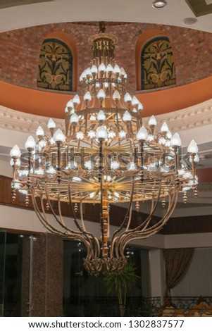 Huge chandelier in the hall. Chandelier on decoarted ceiling of a ballroom. vertical photo.